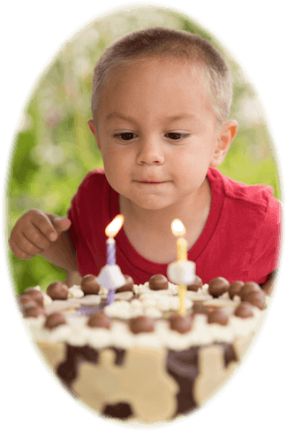 young boy blowing out the candles of his birthday cake